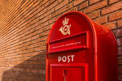 A red danish mailbox on a brick wall. A red danish postbox on a brick wall, Denmark, 30 mars, 2018 Stock Images