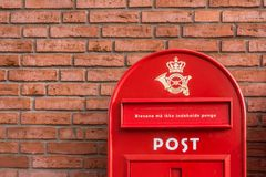 Danish mailbox on a brick wall. A red danish postbox on a brick wall, Denmark, 30 mars, 2018 Royalty Free Stock Photography