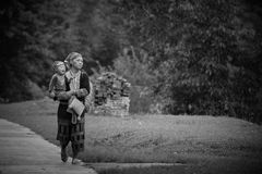 Red Dao hill tribe mother and son. SAPA-JUL 23: Unidentified hill tribe mother with her son walks down from the Red Dao Minority village on July 23, 2012 in Sapa stock images