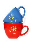 Red and dark blue mugs with yellow flower Royalty Free Stock Photography
