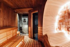 Red, dark sauna with a gray stone stove, canopy and ergonomic cocoon. With a salt wall stock photography