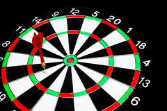 Red dart arrow failed to hit in the target center of dartboard Royalty Free Stock Photos