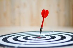 Red dart arrow hit the center target of dartboard metaphor marketing competition concept. On wood background stock image