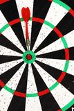 Red dart arrow hit in the target center of dartboard background stock photo