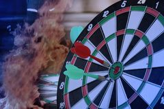 Dart hitting on center with fire on dartboard for business concept. Red dart arrow hitting on Dartboard, Right on target concept using dart in the bulls eye on stock photography