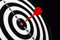 Red dart arrow hitting in the target center of dartboard Stock Photography