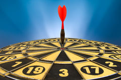Red dart arrow hitting in the target center of dartboard Stock Images