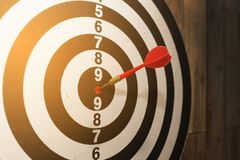 Dart arrow hitting in the target center of dartboard Royalty Free Stock Photo