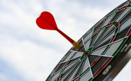 Red dart arrow hitting in the target center of dartboard marketing competition concept, on sky background. Red dart arrow hitting in the target center of royalty free stock photo