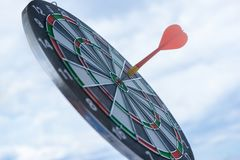 Red dart arrow hitting in the target center of dartboard marketing competition concept, on sky background. Red dart arrow hitting in the target center of stock image