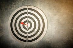 Dart arrow in the target center of dartboard. Red dart arrow in the target center of dartboard Stock Image