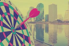 Red Dart Arrow on Target dartboard with blurred city background. Business ...success concept royalty free stock photography