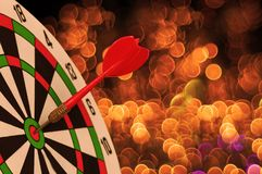 Red Dart Arrow on Target dartboard with Christmas holiday light royalty free stock photography