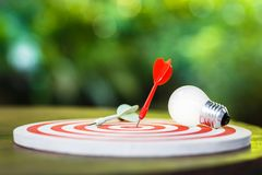 Goal Setting Idea. Red dart hit on the dartboard with white light bulb on the table, smart goal setting royalty free stock photo
