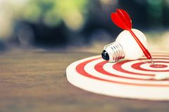 Goal Setting Idea. Red dart hit on the dartboard with white light bulb on the table, smart goal setting stock photography
