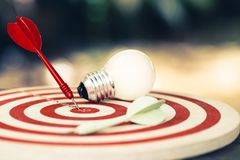 Goal Setting Idea. Red dart hit on the dartboard with white light bulb on the table, smart goal setting royalty free stock image