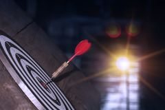Dart hitting on center with fire on dartboard for business concept. royalty free stock photography
