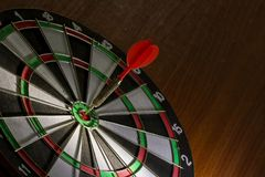 Red Dart hitting center Target, Right on target concept. Red Dart hitting center Target, Right on target concept using dart in the bulls eye on dartboard royalty free stock images