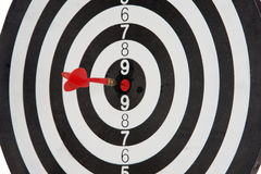 Red dart punctured in the center. Of the target stock photography