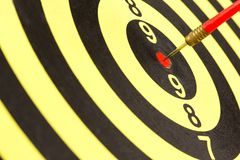 Red dart. Arrow on center of dartboard, metaphor as target success or business goal achievement concept Stock Images