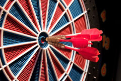 Red darts and dartboard. Red darts and a dartboard Royalty Free Stock Photo