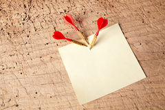 Red darts in a notepad. Three darts in an empty or blank notepad on a vintage wooden board Royalty Free Stock Images