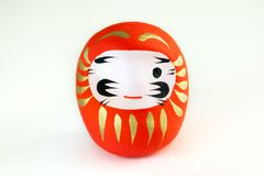 Red Daruma with one eye painted on white background stock photo