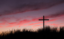 Red Dawn Sky Cross. Black cross on  a sand dune hill with red morning sky Royalty Free Stock Photography