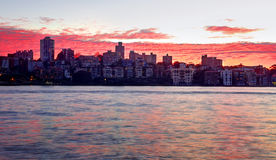 Red dawn sky over Kirribilli, Australia. Rich red dawn sky over Kirribilli buildings and Sydney Harbour.  The rippled clouds resemble water Stock Photo