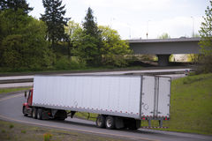 Red day cab semi truck turn on highway exit Stock Photo