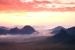 Red daybreak. Misty daybreak in a beautiful hills. Peaks of hills are sticking out from foggy background, the fog is red and orang. E due to Sun rays Stock Image