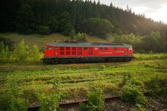 Red DB Schenker DR Class 130 Ludmila locomotive. In summer rain waits for cement freight cars in Bicaz city royalty free stock photos