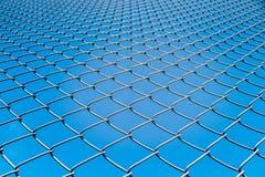 Red de la cerca o del metal de alambre en fondo del cielo azul Foto de archivo