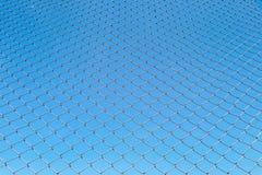 Red de la cerca o del metal de alambre en fondo del cielo azul Imagen de archivo