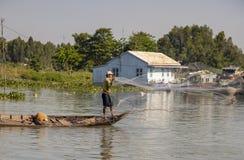Red de pesca del hombre del barco de madera en Chau doc. en Vietnam fotos de archivo