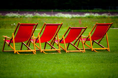 Red deck chair on a green lawn Royalty Free Stock Photo