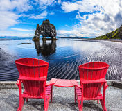 Red deck chairs set in front of Rock stock photo