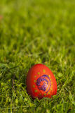 Red decorated Easter egg on the grass Stock Image