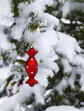 Red decoration on conifer branch. Red New Year decoration hanging on natural conifer branch in snow. Winter seasonal holidays background, New Year and Christmas stock photo