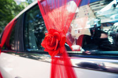 Red decoration of the wedding car. Wedding car decorated with red flowers Stock Photos