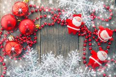 Christmas decoration, red, rustic and  white. Red decorative balls, red beads, Santa, snowflakes and shining stars on a wooden base Stock Photo