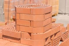 Red decorative bricks with bevelled angle on an outdoor warehouse. Stack of the red perforated decorative bricks with bevelled angle on a blurred background of stock images