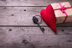 Red decorative  heart, vintage key and gift box  on aged wooden Stock Image