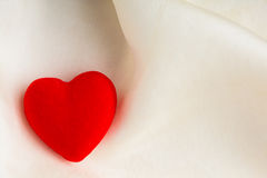 Red decorative heart on white silk background. Royalty Free Stock Photography