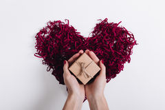 Red decorative heart and a woman's hands holding a box with a gi. Ft, top view Stock Images