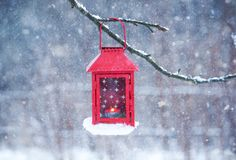 Red lantern hanging on branch. Snowy winter morning in park. Red decorative lantern with candle hanging on the tree branch. Snowy winter evening in park Stock Image