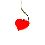 Red decorative plastic heart on the black fishing hook on the wh Royalty Free Stock Images