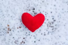 Red plush heart on snow. stock image