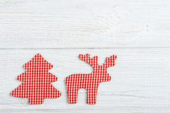Red decorative toy deer on rustic white wooden table Royalty Free Stock Image
