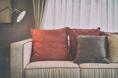 Red and deep brown linen pillows on beige linen sofa with a brass lamp Royalty Free Stock Image